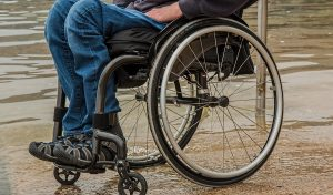 Descripción gráfica: sobre un fondo café, persona en silla de ruedas, la cual se observa desde la cintura hacia abajo, enfocando en gran parte la silla de ruedas en primer plano.