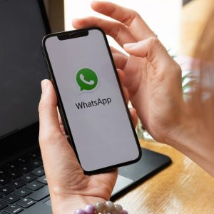 Descripción gráfica: de izquierda a derecha,, de fondo se ve un notebook, en primer plano dos manos sosteniendo un smartphone, el cual tiene la pantalla encendida, donde sobre un fondo blanco se encuentra el logo de WhatsApp.