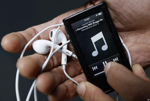Descripción gráfica: sobre un fondo gris, en primer plano, sobre una mano, dispositivo de música con unos audífonos blancos.